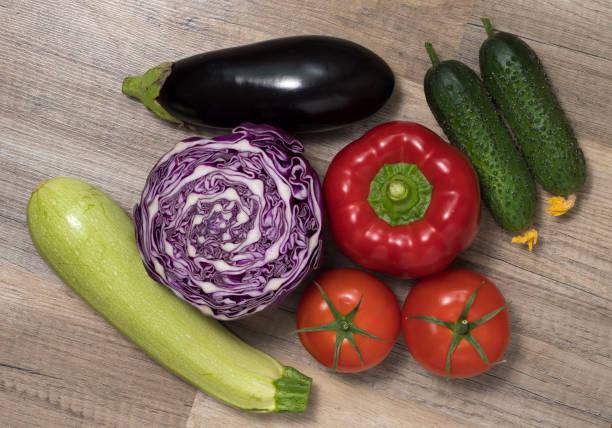Verschiedenes Gemüse (Zucchini, Gurken, Auberginen, Tomaten, Kohl) zusammen auf Holztisch gelegt. – Foto