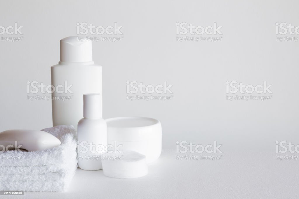 Different white beauty products on the gray background. Cares about...