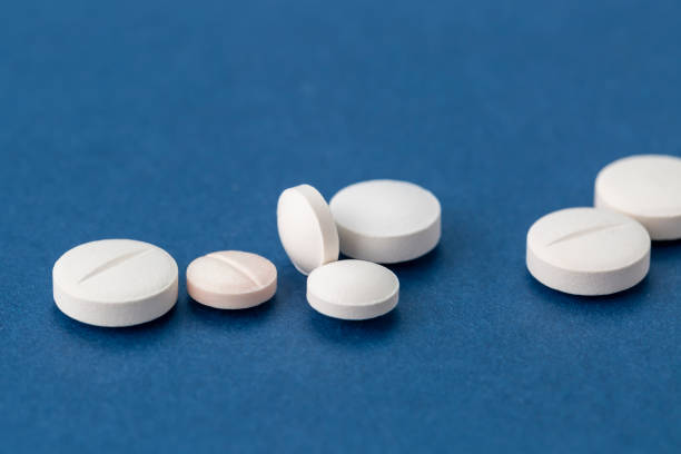 different white pills on blue background stock photo