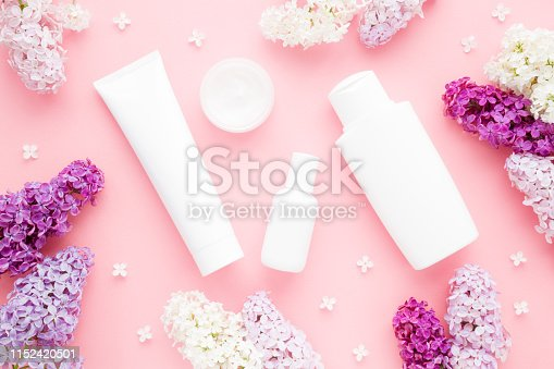 istock Different white toiletries and colorful lilac branches with petals on light pink table. Care about face, hands, legs and body skin. Women beauty products. Empty place for logo on bottles. Flat lay. 1152420501