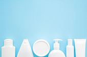 Different white toiletries on light pastel blue table. Care about face, hands, legs and body skin. Women beauty products. Empty place for text or logo. Flat lay. Top view.