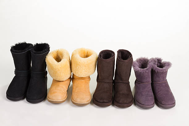 different winter boots on a white background. - lammfellstiefel stock-fotos und bilder