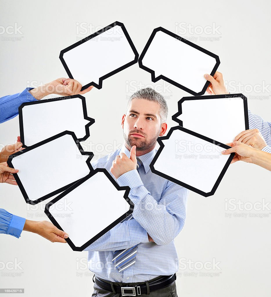 Difficult choice Portrait of serious businessman surrounded by many speech bubbles with copyspace. 30-34 Years Stock Photo