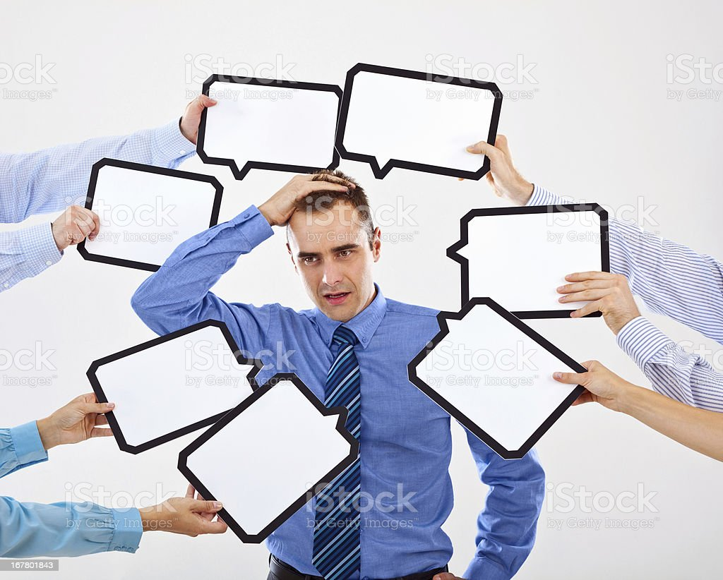 Difficult choice Portrait of confused businessman surrounded by many speech bubbles with copyspace. 30-34 Years Stock Photo