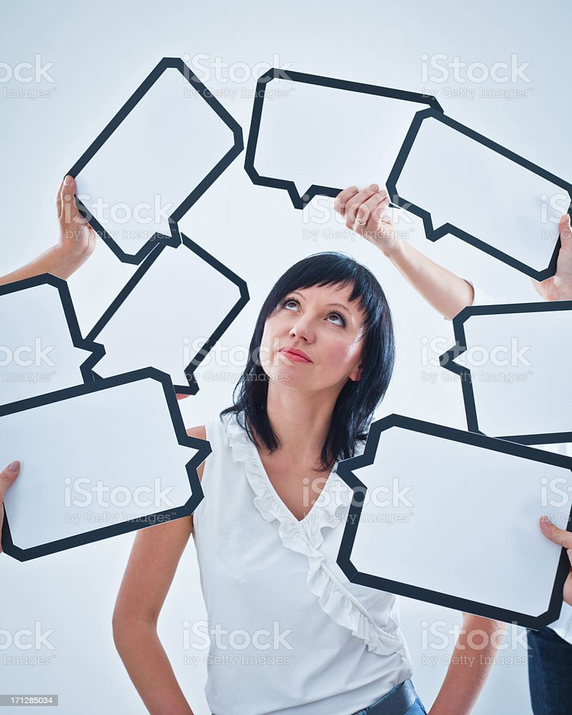 Difficult choice Cofused woman surrounded by many speech bubbles with copyspace, looking up. 30-34 Years Stock Photo