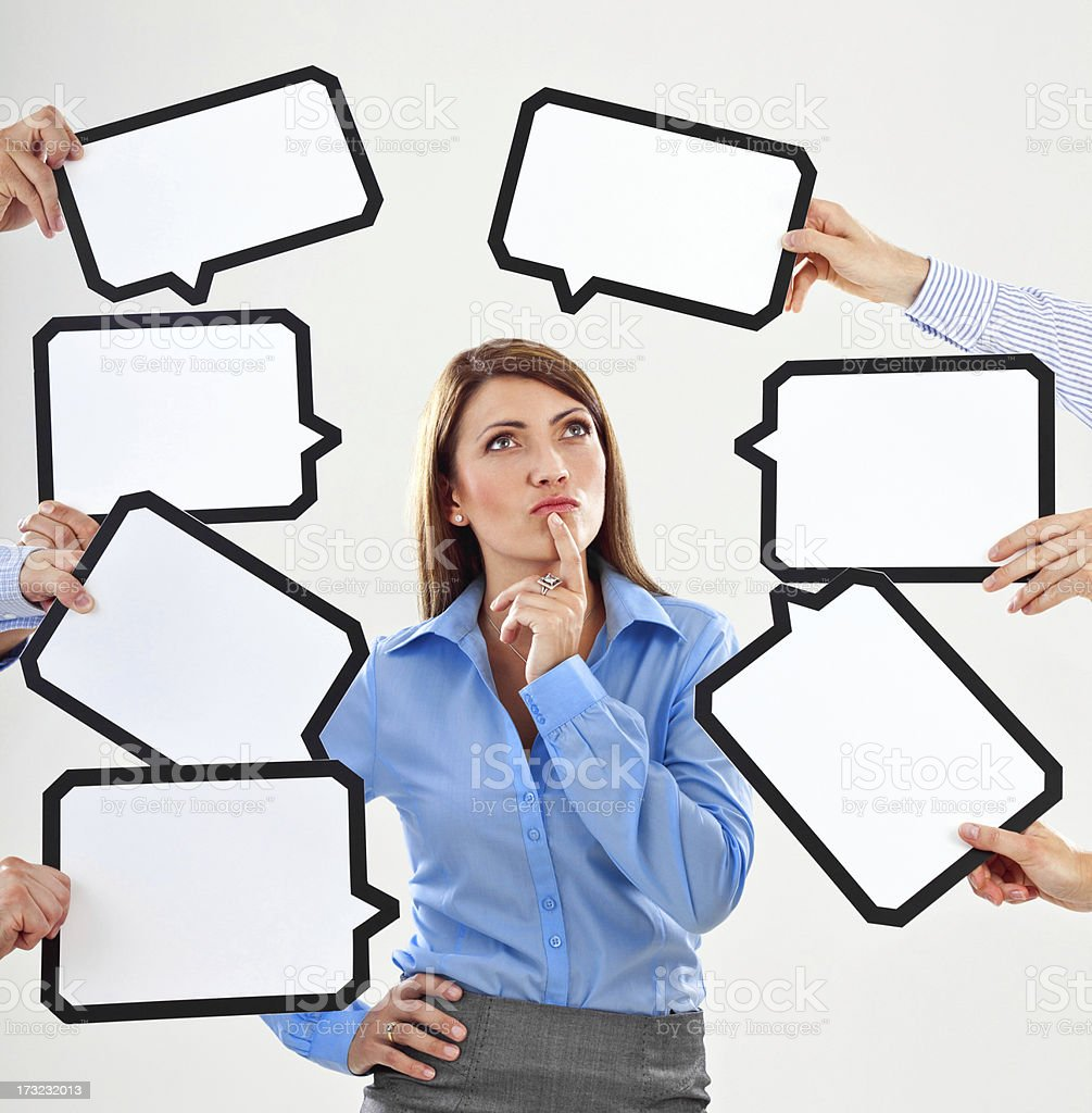 Difficult choice Attractive businesswoman surrounded by many speech bubbles with copyspace, looking up. 25-29 Years Stock Photo