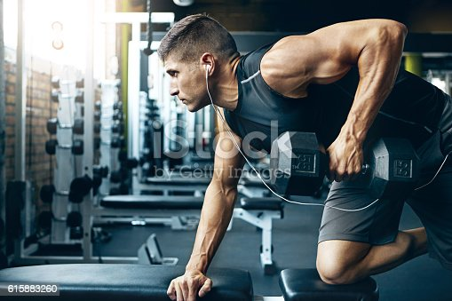 Shot of a man doing weight training at the gym