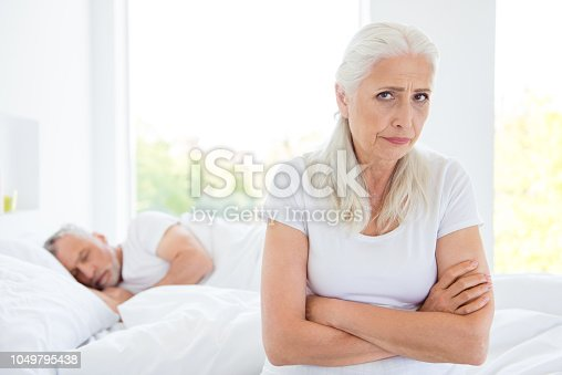 istock Difficult problem situation in relationship concept. Offended woman looks directly into the camera with her hands crossed on the chest on the background of a sleeping husband 1049795438