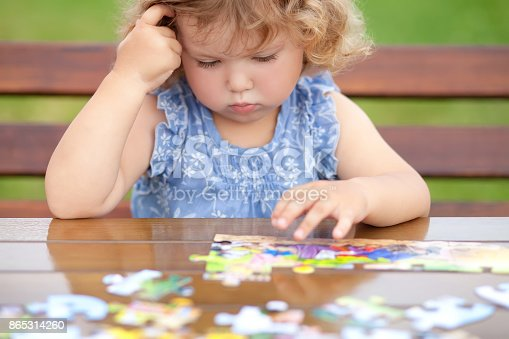istock Difficult task. Tired child playing jigsaw with serious face. 865314260