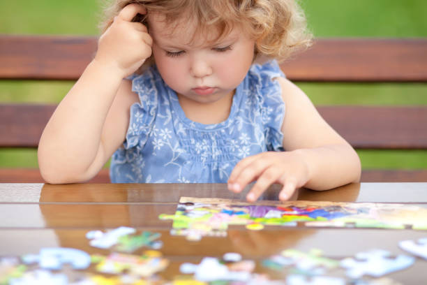 Difficult task. Tired child playing jigsaw with serious face. stock photo