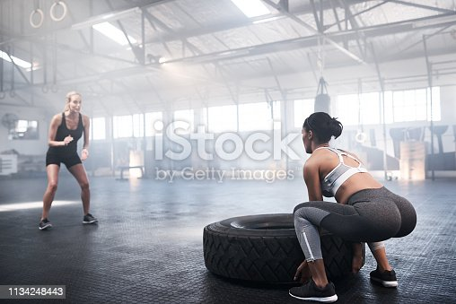 Shot of young women lifting a tyre in the gym with her coach cheering her on