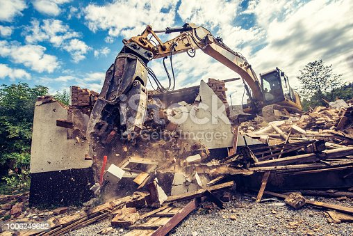 Excavator driving on rubble and demolishing a building on a sunny day.