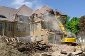 digger demolishing houses for reconstruction.