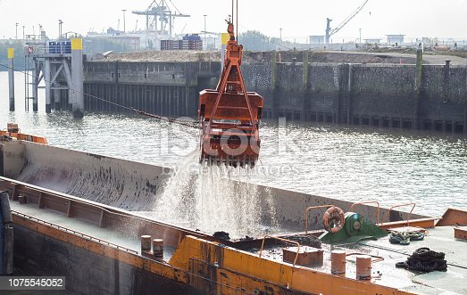 Digger is excavating sediments from the river bed inside the port Hamburg, Germany