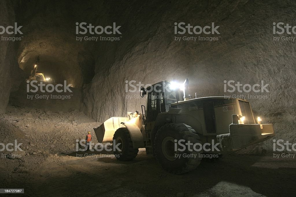 Digger working in a mine underground stock photo