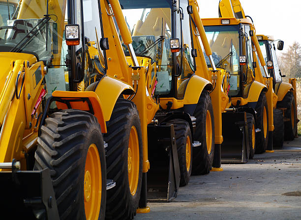 Diggers in a Row on Industrial Parking Lot  construction machinery stock pictures, royalty-free photos & images