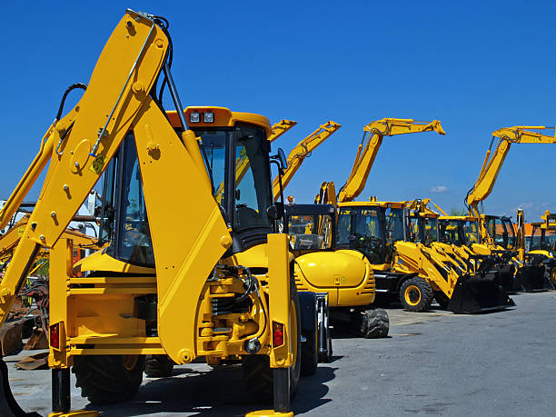 Diggers in a Row on Industrial Parking Lot New, shiny and modern yellow excavator machines waiting on buyers.  construction machinery stock pictures, royalty-free photos & images