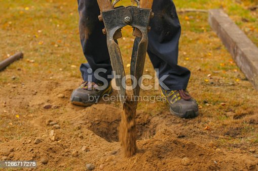 Someone digging a hole in soil with hand tools for a fence post