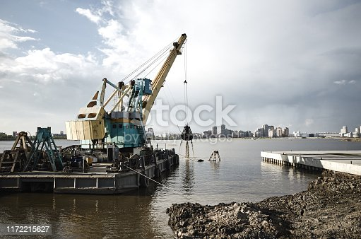 Digging from the bottom of the river, loading a barge and making a pier. Kazan city, Russia