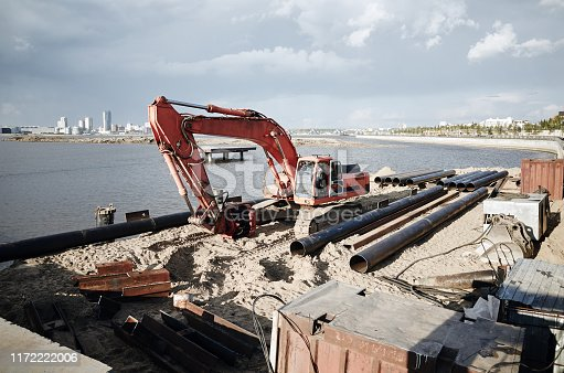 Digging excavator on river coast and making a pier. Kazan city, Russia