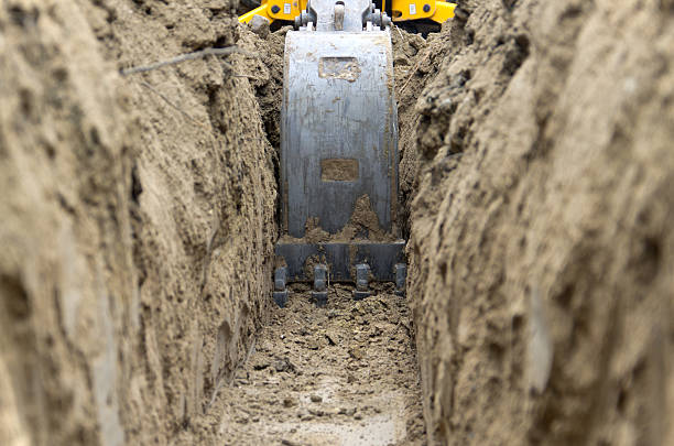 digging power line trench - graven stockfoto's en -beelden