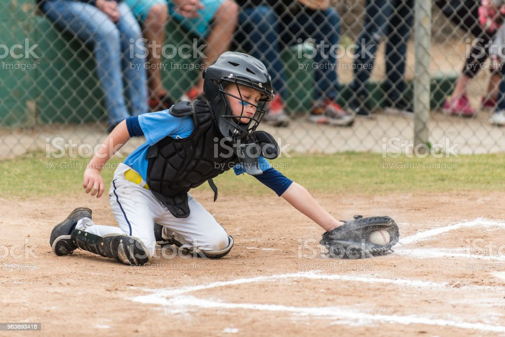 Digging the low pitch out of the batters box. stock photo