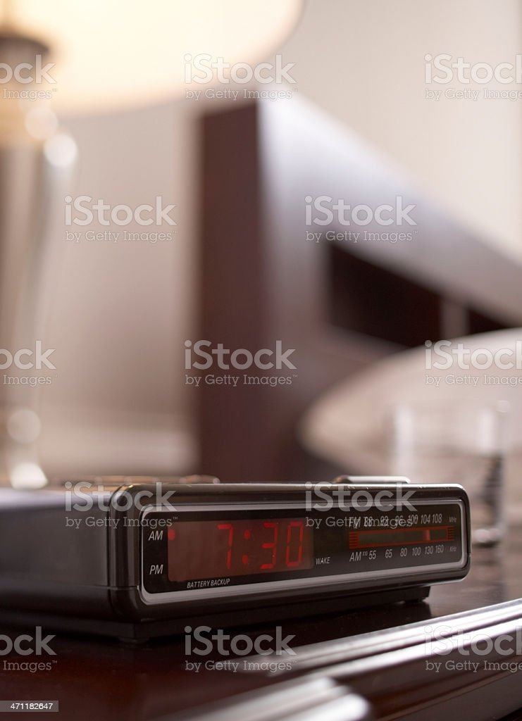Digital alarm clock next to a bed showing 7:30 stock photo