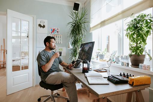 Photo series of Japanese digital artist at his home studio taking a coffee break.
