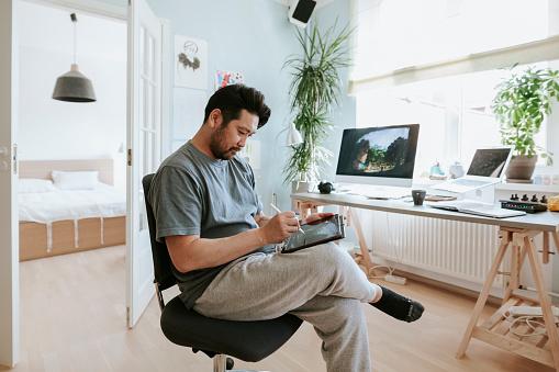 Digital artist drawing on digital table in his home studio