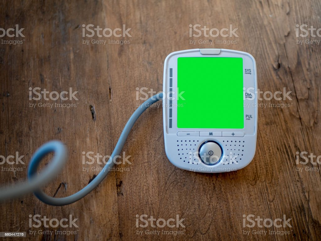 Digital Blood Pressure Monitor on wood background. Pre-keyed Green screen display. Put your own text or data. Medical device. stock photo