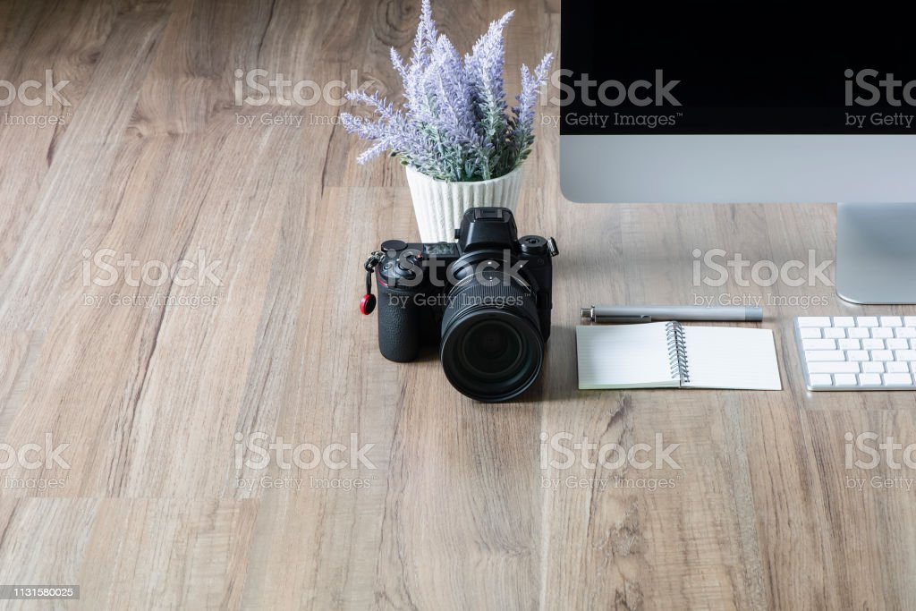 Digital camera, desktop computer and houseplant on wooden table...