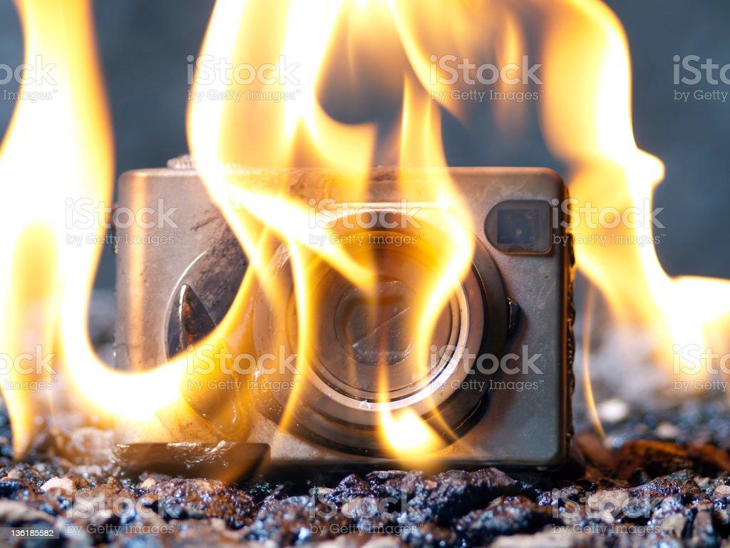 Digital camera on fire stock photo