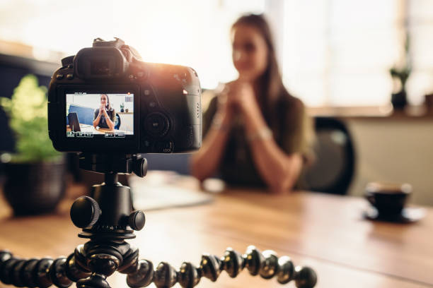 digital camera on flexible tripod recording a video of woman at desk. - camera photographic equipment stock photos and pictures