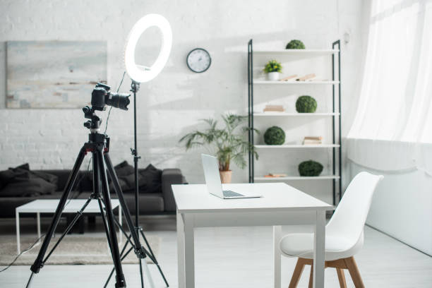 digital camera on tripod near ring lamp and table with laptop stock photo