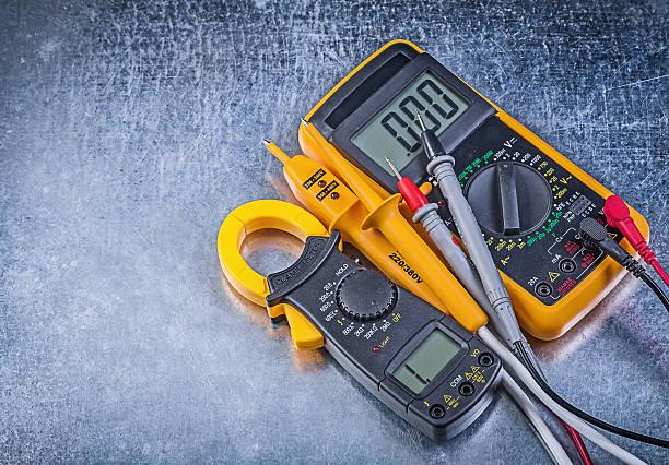 Digital clamp meter electric tester multimeter on metallic backg stock photo