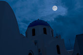 Digital composite image of a full moon over a semi-silhouetted  church in Oia on the Greek Cyclades Island of Santorini.