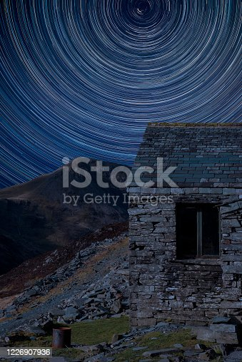 Digital composite image of star trails around Polaris with Autumn Fall landscape image of old bothy in Lake District mountains