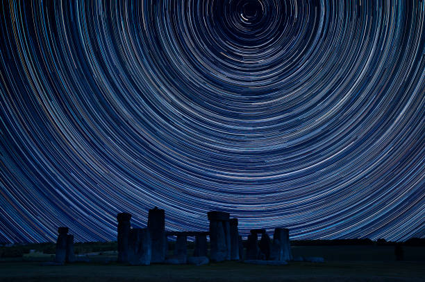 Digital composite image of star trails around Polaris with Stonehenge, a megalithic monument in England built around 3000BC stock photo