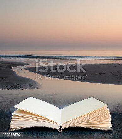 Digital composite of Stunning colorful vibrant sunrise over low tide beach landscape peaceful scene in pages of open book