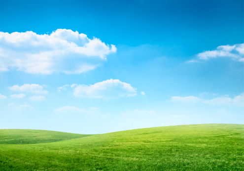 Beneath the light dusting of clouds in a crystal clear, cool-blue sky, an idyllic verdant meadow stretches out across a seemingly endless landscape of gentle hills.  The grass is lush, long and vibrantly colored in several striking shades of green.