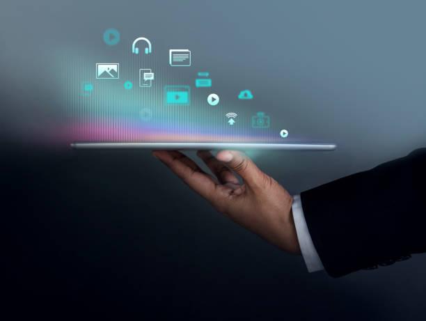 digital contents marketing concept. businessman holding tablet to present many icons, side view, dark tone - inbound marketing imagens e fotografias de stock