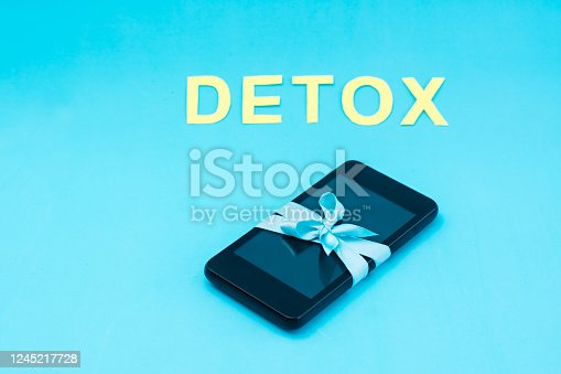 Digital detox concept. The smartphone is tied with a blue ribbon and the word detox on a blue background. Gadget addiction