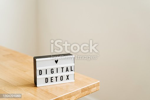 Digital detox day. Lightbox on wooden background and white walls.