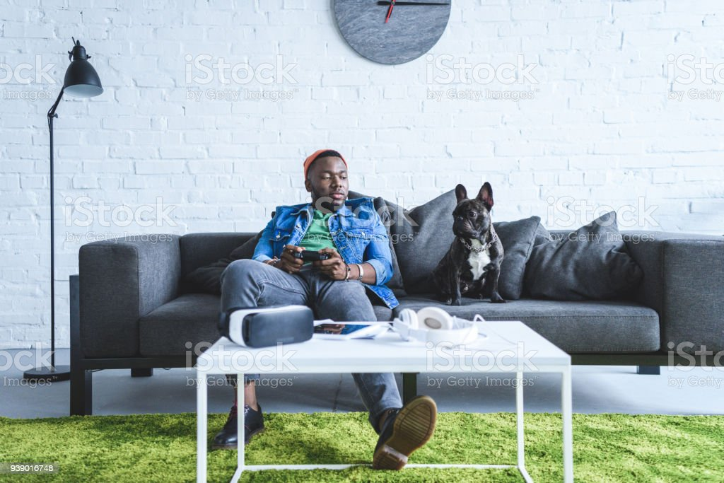 Digital devices on table in front of young man holding joystick and sitting om sofa by French bulldog stock photo