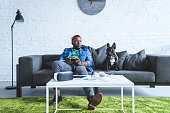 Digital devices on table in front of young man holding joystick and sitting om sofa by French bulldog