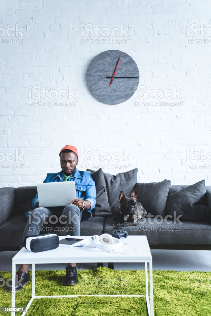 Digital devices on table in front of young man working on laptop and sitting om sofa by French bulldog stock photo