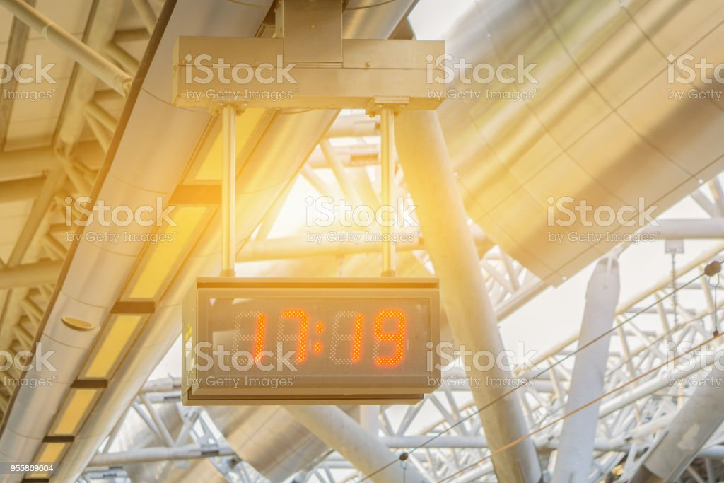 Digital LED clock with red light hanging on the ceiling for time telling in the airport or train station,The Subway  , with many line of lights nearby ,slective focus vintage color stock photo