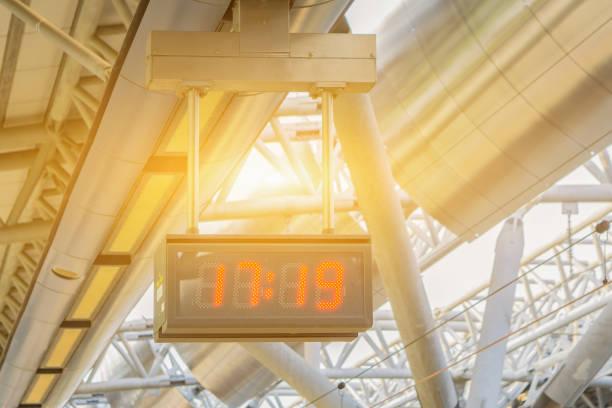 digitale led-uhr mit rotem licht an der decke mal erzählen in den flughafen oder bahnhof, die u-bahn mit vielen lichtern in der nähe, slective focus vintage farbe hängen - led uhr stock-fotos und bilder