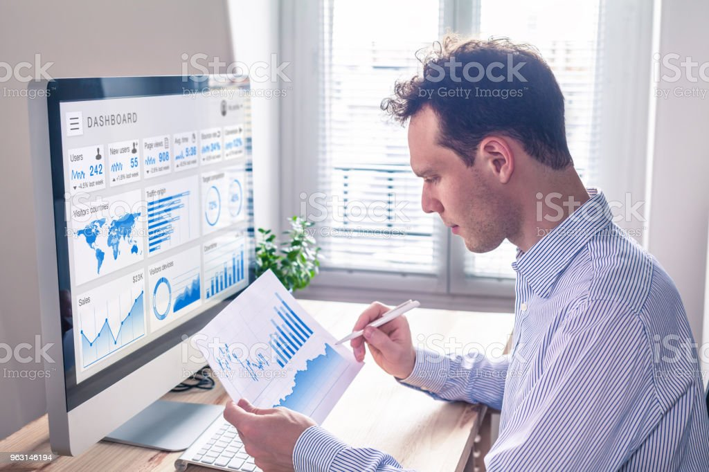 Digital marketing analytics technology with metrics and key performance indicators dashboard on computer screen, person analyzing data chart and advertisement campaign strategy in office stock photo