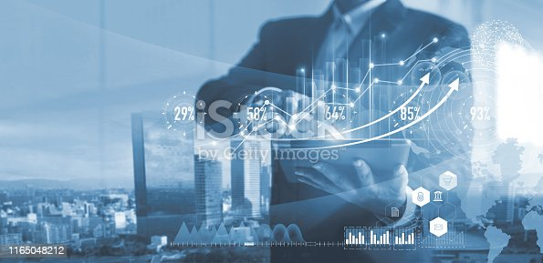 865596974istockphoto Digital marketing. Business strategy. Businessman using tablet analyzing sales data and economic growth graph chart on hologram screen. Business strategy and digital data. 1165048212